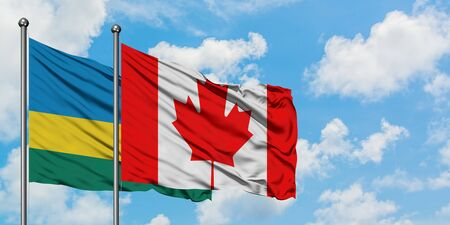 Rwanda and Canada flag waving in the wind against white cloudy blue sky together. Diplomacy concept, international relations.