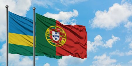 Rwanda and Portugal flag waving in the wind against white cloudy blue sky together. Diplomacy concept, international relations. Archivio Fotografico