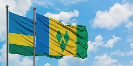 Rwanda and Saint Vincent And The Grenadines flag waving in the wind against white cloudy blue sky together. Diplomacy concept, international relations. Archivio Fotografico