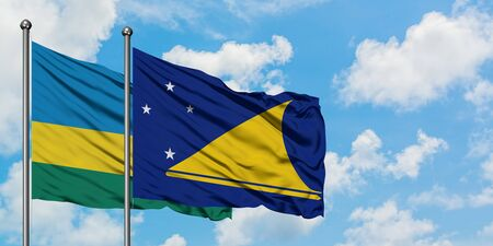 Rwanda and Tokelau flag waving in the wind against white cloudy blue sky together. Diplomacy concept, international relations.