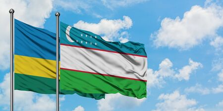 Rwanda and Uzbekistan flag waving in the wind against white cloudy blue sky together. Diplomacy concept, international relations.