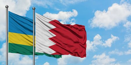 Rwanda and Bahrain flag waving in the wind against white cloudy blue sky together. Diplomacy concept, international relations.