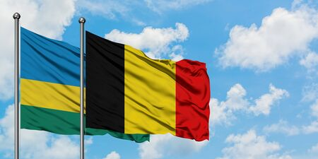 Rwanda and Belgium flag waving in the wind against white cloudy blue sky together. Diplomacy concept, international relations.