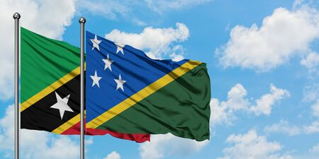 Saint Kitts And Nevis and Solomon Islands flag waving in the wind against white cloudy blue sky together. Diplomacy concept, international relations. Stok Fotoğraf
