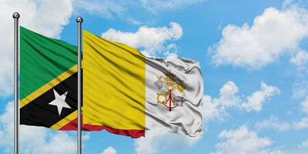 Saint Kitts And Nevis and Vatican City flag waving in the wind against white cloudy blue sky together. Diplomacy concept, international relations.