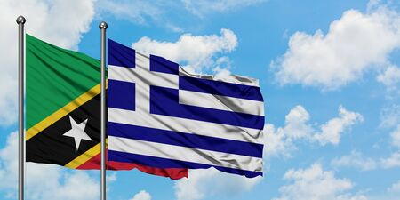Saint Kitts And Nevis and Greece flag waving in the wind against white cloudy blue sky together. Diplomacy concept, international relations.