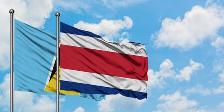 Saint Lucia and Costa Rica flag waving in the wind against white cloudy blue sky together. Diplomacy concept, international relations.