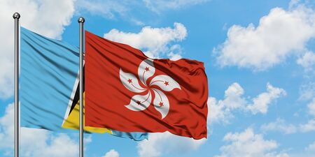 Saint Lucia and Hong Kong flag waving in the wind against white cloudy blue sky together. Diplomacy concept, international relations.