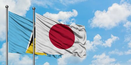 Saint Lucia and Japan flag waving in the wind against white cloudy blue sky together. Diplomacy concept, international relations.