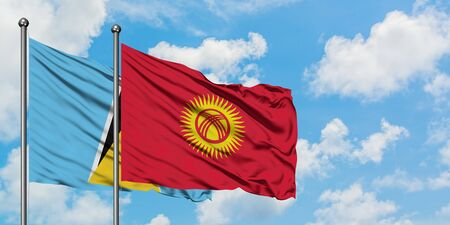 Saint Lucia and Kyrgyzstan flag waving in the wind against white cloudy blue sky together. Diplomacy concept, international relations.