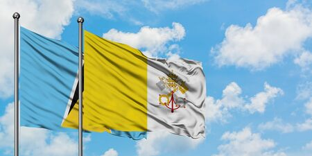 Saint Lucia and Vatican City flag waving in the wind against white cloudy blue sky together. Diplomacy concept, international relations. 版權商用圖片