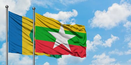 Saint Vincent And The Grenadines and Myanmar flag waving in the wind against white cloudy blue sky together. Diplomacy concept, international relations. Stok Fotoğraf