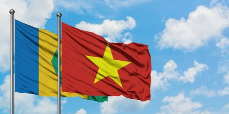 Saint Vincent And The Grenadines and Vietnam flag waving in the wind against white cloudy blue sky together. Diplomacy concept, international relations.