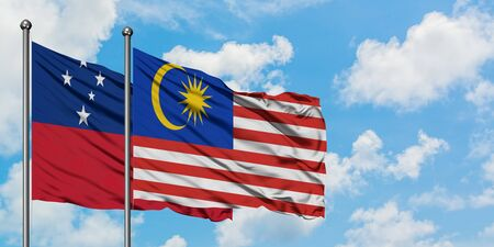Samoa and Malaysia flag waving in the wind against white cloudy blue sky together. Diplomacy concept, international relations.