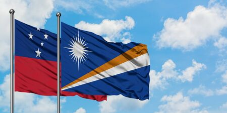 Samoa and Marshall Islands flag waving in the wind against white cloudy blue sky together. Diplomacy concept, international relations. 免版税图像
