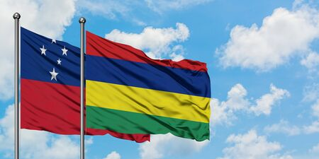 Samoa and Mauritius flag waving in the wind against white cloudy blue sky together. Diplomacy concept, international relations. 免版税图像