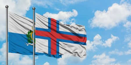 San Marino and Faroe Islands flag waving in the wind against white cloudy blue sky together. Diplomacy concept, international relations. 免版税图像