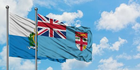 San Marino and Fiji flag waving in the wind against white cloudy blue sky together. Diplomacy concept, international relations. 免版税图像