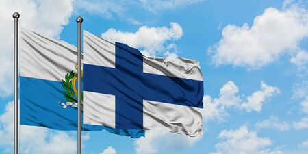 San Marino and Finland flag waving in the wind against white cloudy blue sky together. Diplomacy concept, international relations.