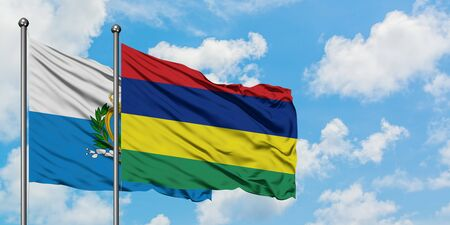 San Marino and Mauritius flag waving in the wind against white cloudy blue sky together. Diplomacy concept, international relations.