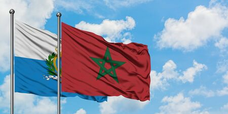 San Marino and Morocco flag waving in the wind against white cloudy blue sky together. Diplomacy concept, international relations. 免版税图像