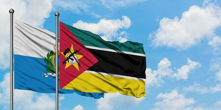 San Marino and Mozambique flag waving in the wind against white cloudy blue sky together. Diplomacy concept, international relations.