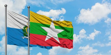 San Marino and Myanmar flag waving in the wind against white cloudy blue sky together. Diplomacy concept, international relations.