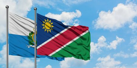 San Marino and Namibia flag waving in the wind against white cloudy blue sky together. Diplomacy concept, international relations. 免版税图像