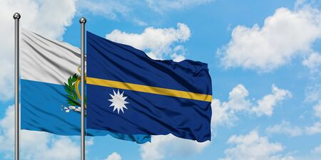 San Marino and Nauru flag waving in the wind against white cloudy blue sky together. Diplomacy concept, international relations. 免版税图像