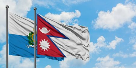 San Marino and Nepal flag waving in the wind against white cloudy blue sky together. Diplomacy concept, international relations. 免版税图像