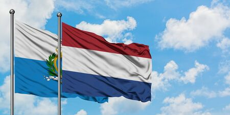 San Marino and Netherlands flag waving in the wind against white cloudy blue sky together. Diplomacy concept, international relations.