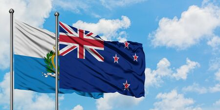 San Marino and New Zealand flag waving in the wind against white cloudy blue sky together. Diplomacy concept, international relations.