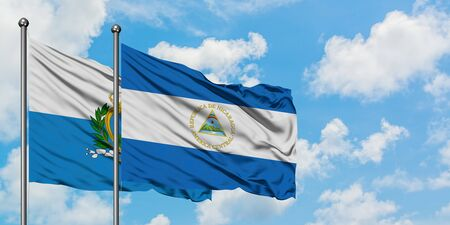 San Marino and Nicaragua flag waving in the wind against white cloudy blue sky together. Diplomacy concept, international relations. 免版税图像