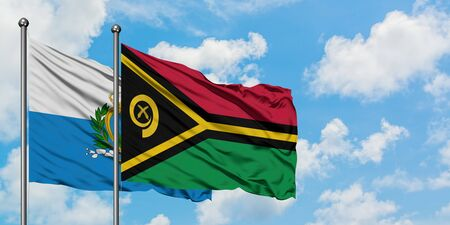 San Marino and Vanuatu flag waving in the wind against white cloudy blue sky together. Diplomacy concept, international relations. 免版税图像
