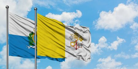 San Marino and Vatican City flag waving in the wind against white cloudy blue sky together. Diplomacy concept, international relations.