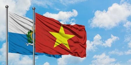 San Marino and Vietnam flag waving in the wind against white cloudy blue sky together. Diplomacy concept, international relations.
