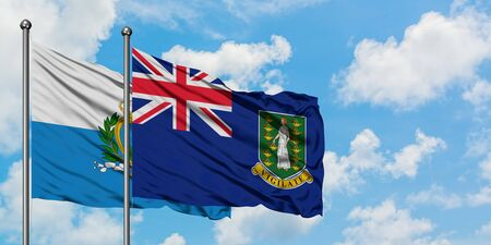 San Marino and British Virgin Islands flag waving in the wind against white cloudy blue sky together. Diplomacy concept, international relations.