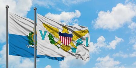 San Marino and United States Virgin Islands flag waving in the wind against white cloudy blue sky together. Diplomacy concept, international relations.