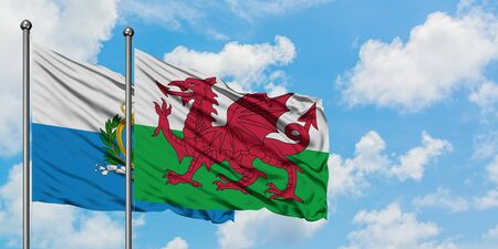 San Marino and Wales flag waving in the wind against white cloudy blue sky together. Diplomacy concept, international relations.
