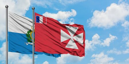 San Marino and Wallis And Futuna flag waving in the wind against white cloudy blue sky together. Diplomacy concept, international relations. 免版税图像