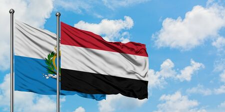 San Marino and Yemen flag waving in the wind against white cloudy blue sky together. Diplomacy concept, international relations. 免版税图像