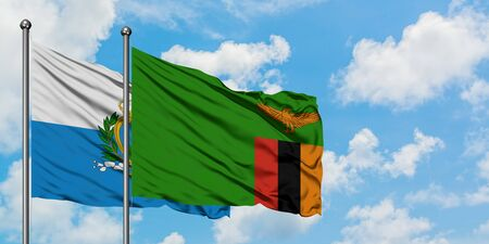 San Marino and Zambia flag waving in the wind against white cloudy blue sky together. Diplomacy concept, international relations.