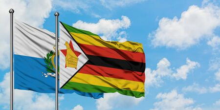 San Marino and Zimbabwe flag waving in the wind against white cloudy blue sky together. Diplomacy concept, international relations.