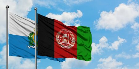 San Marino and Afghanistan flag waving in the wind against white cloudy blue sky together. Diplomacy concept, international relations.