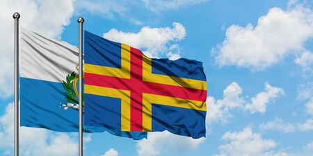 San Marino and Aland Islands flag waving in the wind against white cloudy blue sky together. Diplomacy concept, international relations.