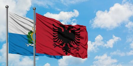 San Marino and Albania flag waving in the wind against white cloudy blue sky together. Diplomacy concept, international relations.