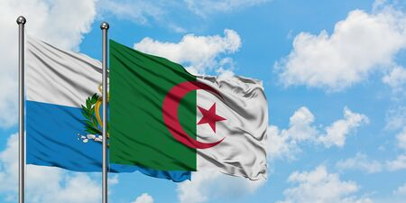 San Marino and Algeria flag waving in the wind against white cloudy blue sky together. Diplomacy concept, international relations.