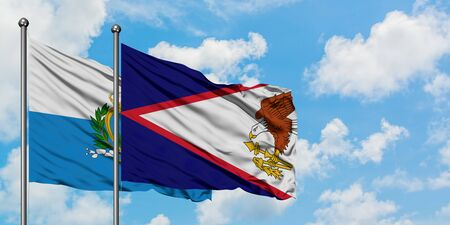 San Marino and American Samoa flag waving in the wind against white cloudy blue sky together. Diplomacy concept, international relations. 免版税图像