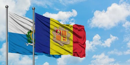 San Marino and Andorra flag waving in the wind against white cloudy blue sky together. Diplomacy concept, international relations.