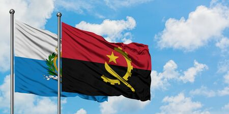 San Marino and Angola flag waving in the wind against white cloudy blue sky together. Diplomacy concept, international relations.